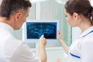 Male dentist showing something on the computer monitor to female nurse at clinic
